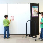 A woman and a young boy look at a poster on a temporary wall while a younger boy draws on a writable surface on the opposing side of the temporary wall