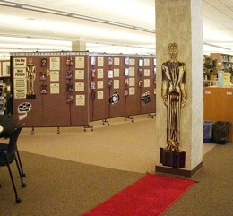Academy Awards paraphernalia is tacked onto a rolling partition for an Oscar trivia contest