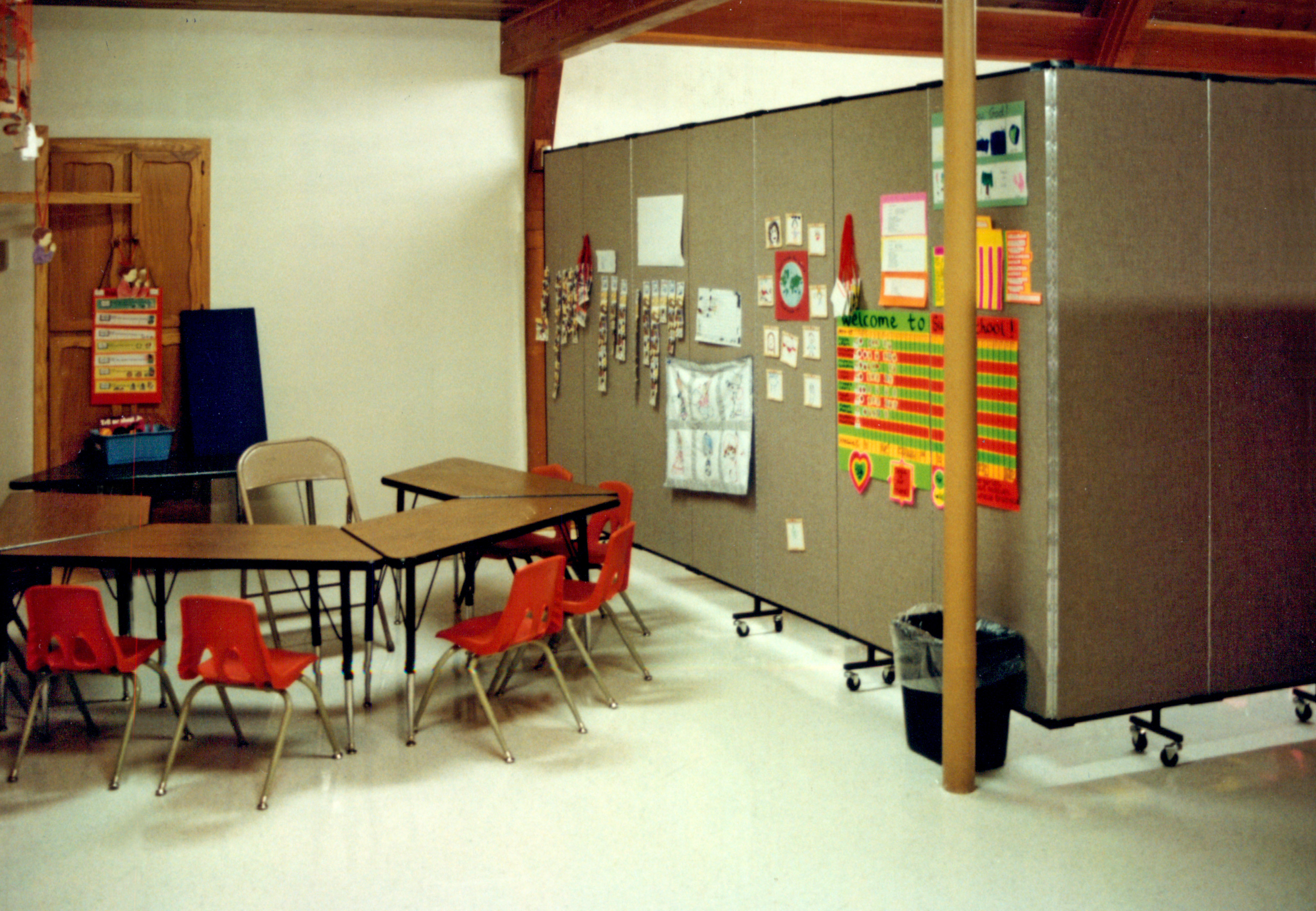 Student tables and chairs next to a room divider panel with educational material tacked to the fabric surface