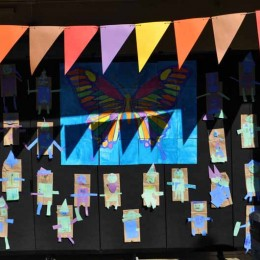Banners hang above paper bag puppet tacked to a black room divider in a courtyard