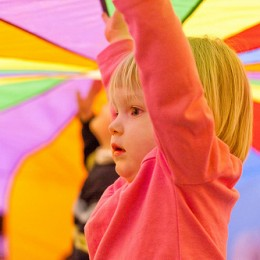 A toddler stands under a colorful parachute during game time