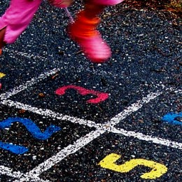 Girl jumping on hopscotch pattern