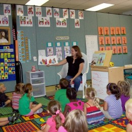A room divider separates a room into two kindergarten classrooms filled with students and teachers
