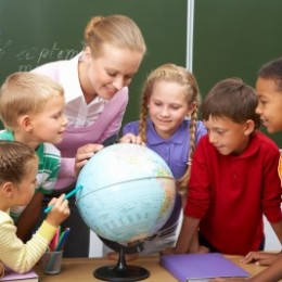 Students and a teacher gather around a globe