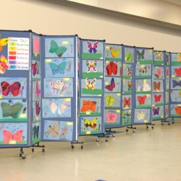 Student artwork displayed on an accordion room divider in a hallway