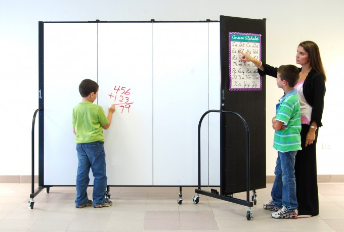 Dual-sided room divider. One side is covered in fabric and the other side is a dry erase board.