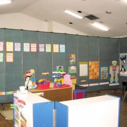 A portable partition forms a classroom in a large open space