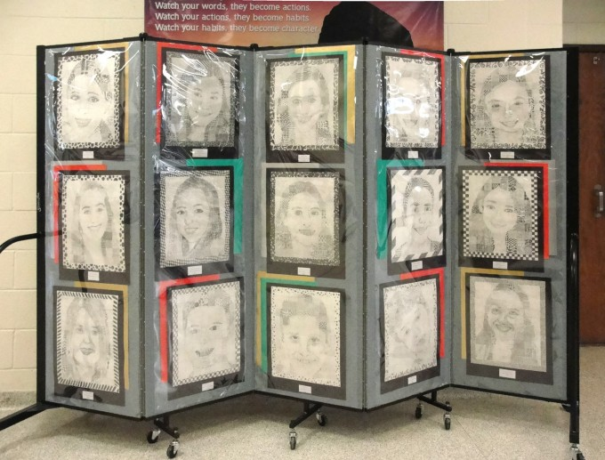 Student self portraits hang on a Screenflex Portable Partition