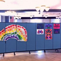 Children's artwork tacked to a Screenflex Room Divider