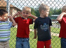 Six kindergarten boys plugging their ears from a loud noise while standing along a chainlink fence.