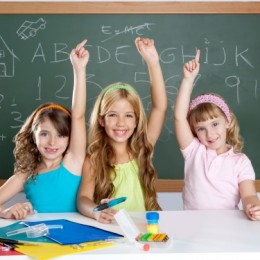 Three smiling young girls raising their hands in front of a chalkboard