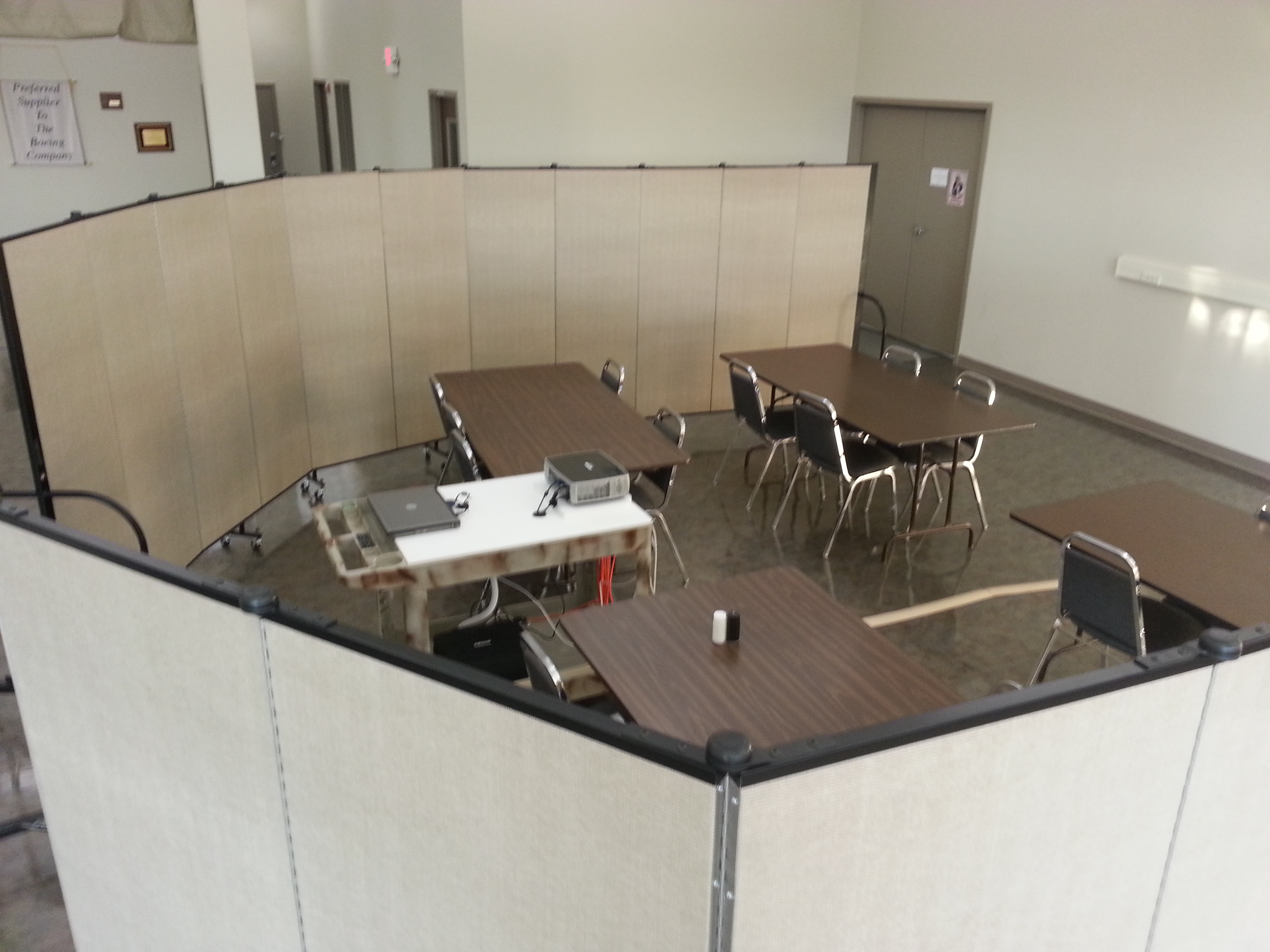 Screenflex Room Dividers are arranged around a group of 4 tables and a projector to create a conference room within a large open meeting area.