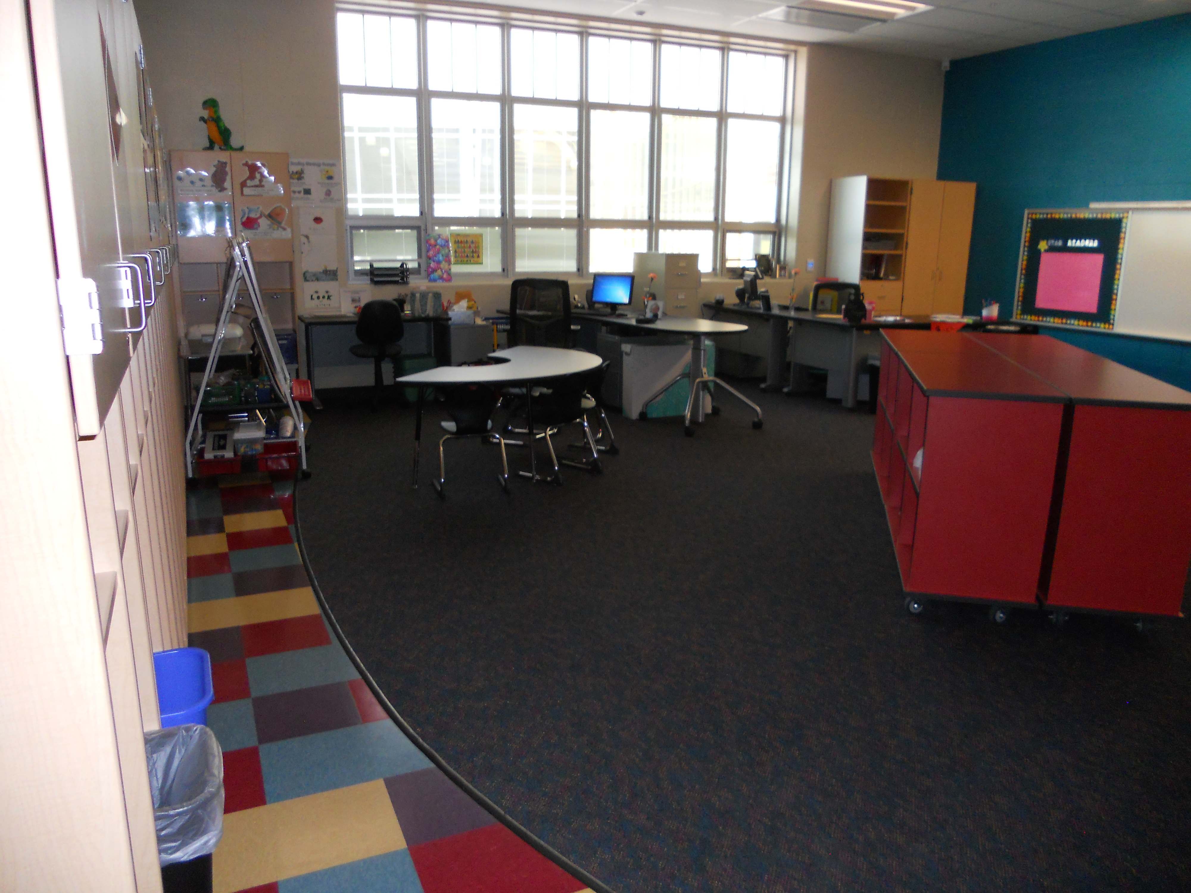 One large classroom cluttered with cabinets and tables and chairs.