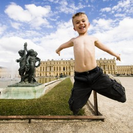 Shirtless boy jumps besides a water sculpture in front of a palace