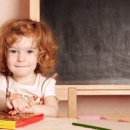 A female preschool student sits at a desk next to a chalkboard.