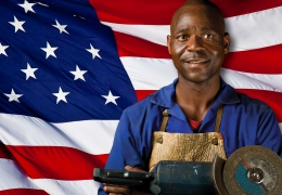 Male holding a grinding tool stands in front of the American Flag.