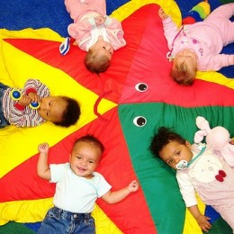 4 infants laying on a play parachute