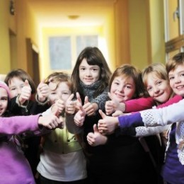 7 elementary girls give a thumbs up in the school hallway.
