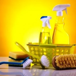 A group of yellow cleaning supplies in a basket.