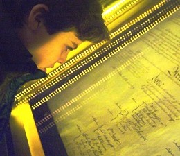 A teen boy looks through the glass containing the US Constitution.