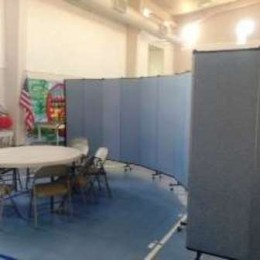 Portable room dividers create a circular room in the corner of a church gym.