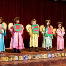 5 elemetary students dressed as angels stand on a stage and hold signs spelling out NOEL.