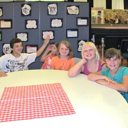 Students sit at a round table at a VBS camp help in a church sanctuary.