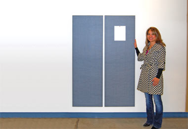 Female stands besides two acounstical wall panels hung vertically on a wall.