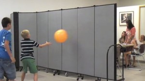 Children bounce a ball against a room divider while students talk with a teacher at a table on the other side of the divider.