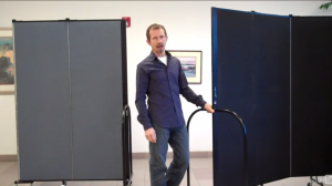 A male stands next to two Screenflex Room Dividers. With one divider unit he demonstrates how to make Corners with Screenflex Room Dividers.