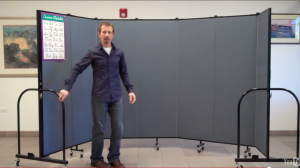 A Screenflex Room Divider is arranged into a curved wall by a man in his office.