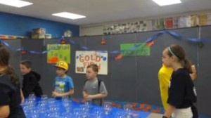 Students play a carnival goldfish bowl game that is arranged on a table in front of a decorated room divider.