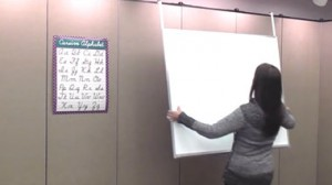 A teacher hangs a dry erase boards onto a Screenflex Room Divider.