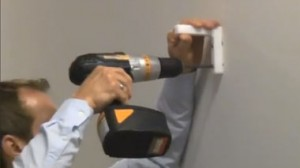 A man uses an electric screwdriver to attach an L bracket to a wall.