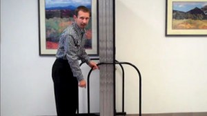 A man stands along side a folded Screenflex Room Divider.