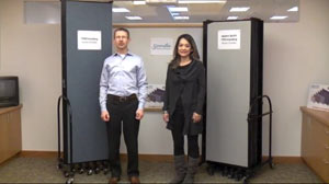 "A male stands beside an 8'0"" room divider next to a female standing next to a 6'0"" room divider."