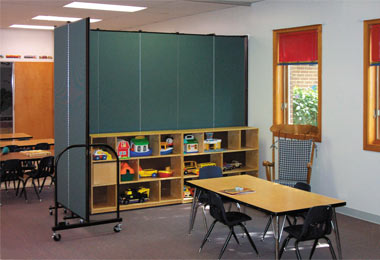 Wall mount room dividers in a day care center are used to create an L shaped wall to divide teaching and play areas.