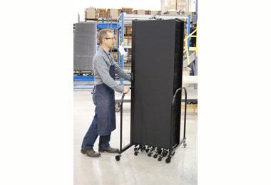 A man rolls a folded Screenflex Welding Screen in a factory.