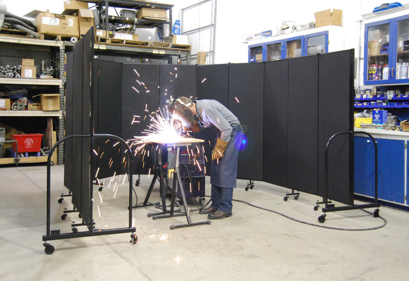 Screenflex Welding Screen surrounds a welder and protects a factory from sparks.