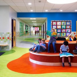 Students reading in a very colorful school hallway with modern seating area.