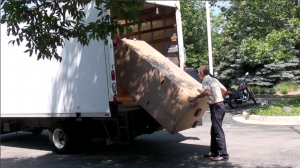 A man unloading a room divider from a truck