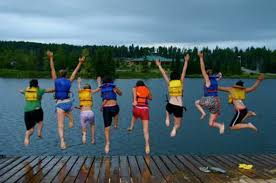 Children jump into a lake off a pier