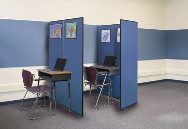 Two blue room dividers divide a set of school desks to create privacy for when needed