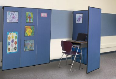 A three panel room divider displays artwork while another divider surrounds a school desk for privacy