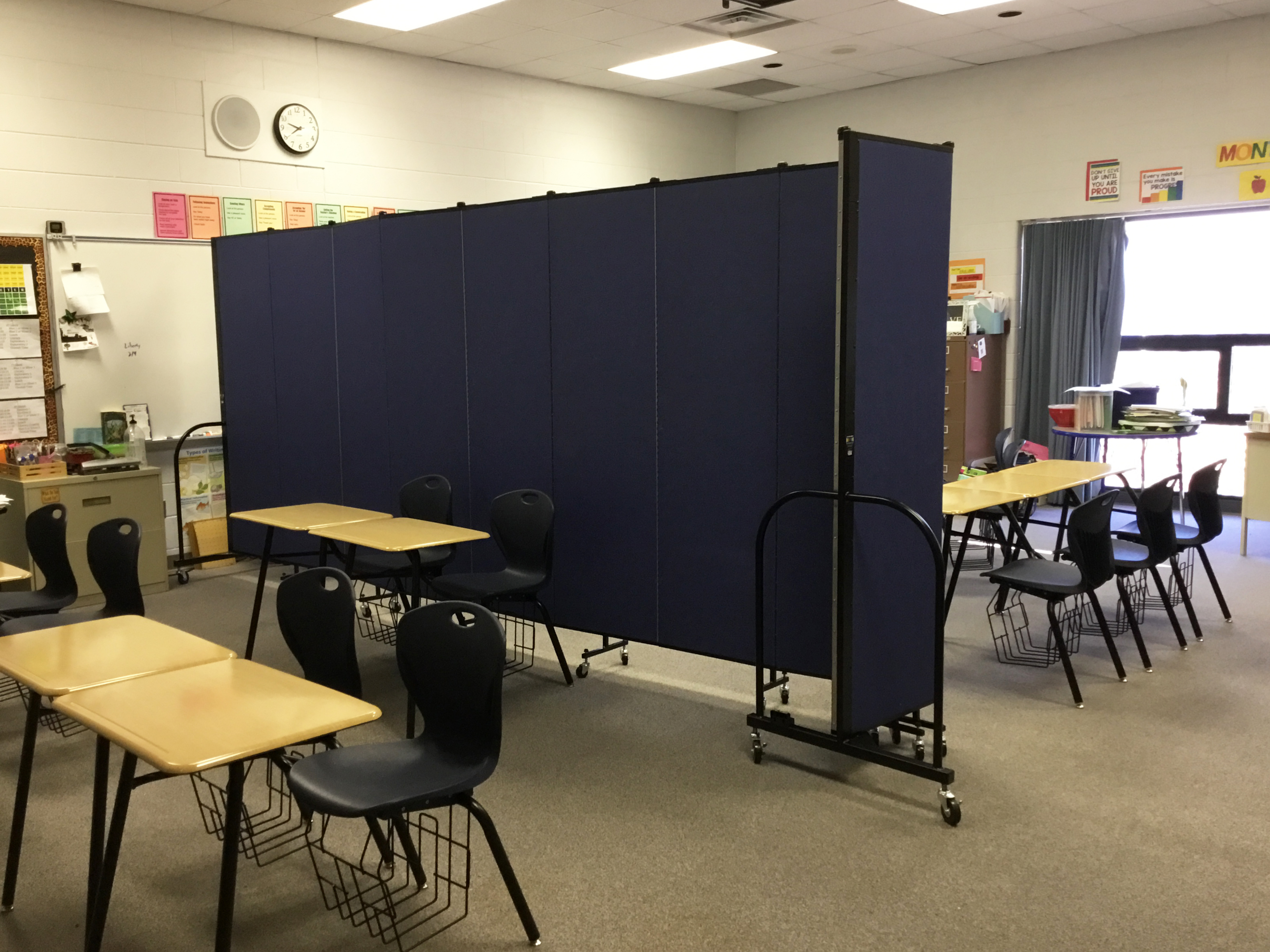 A room divider separates a classroom into two rooms