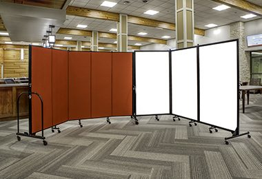 A red portable partition adjoined to a three panel whiteboard partition