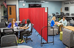 A red Screenflex portable wall divider students in a classroom into two learning groups